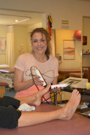 Lisa using laser treatment on a patient